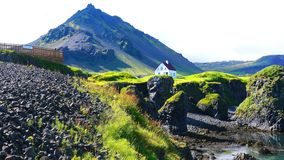 Natural landscape of Coastline with the basalt rocks formation and a lonely house. At Arnarstapi Village in Iceland stock video footage