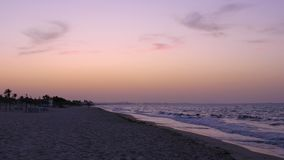 Natural landscape colored sky during evening sunset and sea waves on sandy beach stock footage