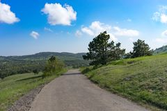 Natural landscape with green field overgrown with grass under the sky with clouds and road. Yalta, Crimea-June 1, 2016: Natural landscape with green field Stock Photos