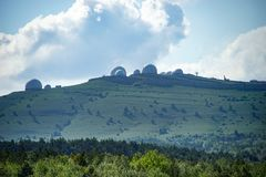Natural landscape with a green hill covered with grass under the sky with clouds and buildings. Yalta, Crimea-June 1, 2016: Natural landscape with a green hill Stock Photos