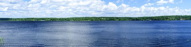 Panorama of the lake and with white clouds. Sunny summer day Royalty Free Stock Photo