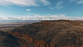 Natural landscape: mountainous terrain, mountainous snow-capped peaks. In the distance on the horizon, yellowed trees. The nature of Siberia: a mountain valley stock footage