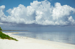 Natural landscape view of Cayo Coco Cuban island beach and tranquil ocean with huge, giant white floating cloud above the water Royalty Free Stock Image
