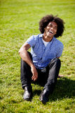 Natural Laugh. An African American sitting on grass with a natural laugh Royalty Free Stock Photo