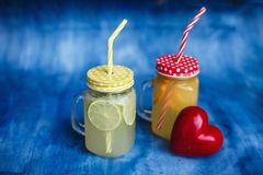 Natural lemonade is poured into two cans standing on a blue background next to the red heart stock images