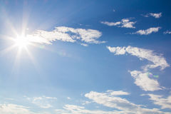 Natural lens flare and radiating rays in  blue sky with clouds Stock Image