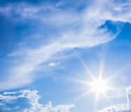 Natural lens flare and radiating rays in a blue sky with clouds Stock Image