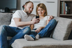 Natural, lifestyle image of attractive couple sitting on couch together looking at smartphone in the living room. Couple sitting on couch together looking at Stock Images