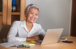 Natural lifestyle office portrait of attractive and happy successful mature Asian woman working at laptop computer desk smiling stock photo