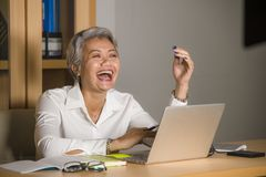 Natural lifestyle office portrait of attractive and happy successful mature Asian woman working at laptop computer desk smiling stock photography