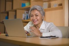 Natural lifestyle office portrait of attractive and happy successful mature Asian woman working at laptop computer desk smiling royalty free stock image