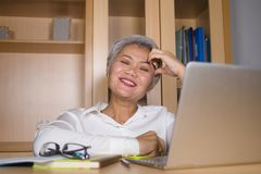 Natural lifestyle office portrait of attractive and happy successful mature Asian woman working at laptop computer desk smiling royalty free stock photo