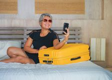 Natural lifestyle portrait of happy and attractive 40s to 50s mature Asian tourist woman with grey hair arriving in hotel room in. Travel and selfie. natural stock photos