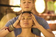 Natural lifestyle portrait of young beautiful and relaxed Asian Balinese woman receiving a healing facial and head Thai massage by stock photo
