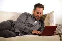 Natural lifestyle portrait of young handsome and successful self employed man working at home using laptop computer lying relaxed. At living couch networking royalty free stock images