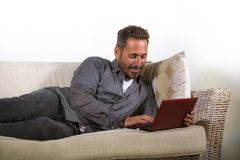 Natural lifestyle portrait of young handsome and successful self employed man working at home using laptop computer lying relaxed. At living couch networking stock image