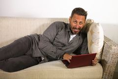 Natural lifestyle portrait of young handsome and successful self employed man working at home using laptop computer lying relaxed. At living couch networking royalty free stock photos