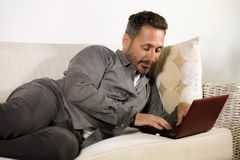 Natural lifestyle portrait of young handsome and successful self employed man working at home using laptop computer lying relaxed. At living couch networking stock photos