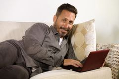 Natural lifestyle portrait of young handsome and successful self employed man working at home using laptop computer lying relaxed. At living couch networking royalty free stock photography