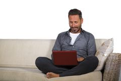 Lifestyle portrait of young handsome and successful self employed man working at home using laptop computer sitting relaxed at. Natural lifestyle portrait of royalty free stock images
