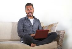Lifestyle portrait of young handsome and successful self employed man working at home using laptop computer sitting relaxed at. Natural lifestyle portrait of royalty free stock photos
