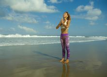 Natural lifestyle portrait of young happy and attractive fit and slim blond woman doing yoga and relaxation exercise outdoors at. Beautiful beach in relax and royalty free stock images
