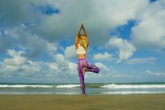 Natural lifestyle portrait of young happy and attractive fit and slim blond woman doing yoga and relaxation exercise outdoors at. Beautiful beach in relax and stock photo