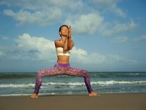 Natural lifestyle portrait of young happy and attractive fit and slim blond woman doing yoga and relaxation exercise outdoors at. Beautiful beach in relax and royalty free stock photography