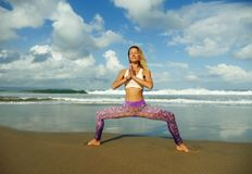 Natural lifestyle portrait of young happy and attractive fit and slim blond woman doing yoga and relaxation exercise outdoors at. Beautiful beach in relax and stock photos