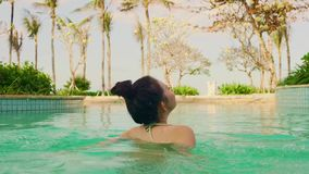 Natural lifestyle shot on young happy and beautiful Asian Korean woman in bikini enjoying Summer holiday getaway at luxury hotel. Natural lifestyle shot on young stock video