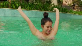Natural lifestyle shot on young happy and beautiful Asian Korean woman in bikini enjoying Summer holiday getaway at luxury hotel. Natural lifestyle shot on young stock footage