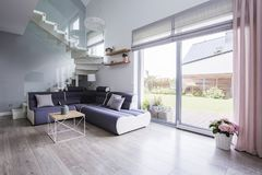 Natural light coming through big glass door to a monochromatic,. Open space living room interior with a modern sofa on hardwood floor royalty free stock images