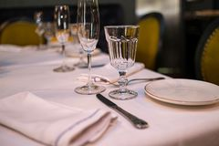 Natural light or daylight shot of modern restaurant table set for a lunch. Shallow focus on wine glass. Empty glasses set in. Restaurant. Close up photo of a stock photo