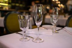 Natural light or daylight shot of modern restaurant table set for a lunch. Shallow focus on wine glass. Empty glasses set in. Restaurant. Close up photo of a stock photos