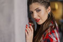Natural light indoor portrait of young pretty girl with long dark brown hair, natural makeup and red lips. Stylish woman. Looking at you royalty free stock image