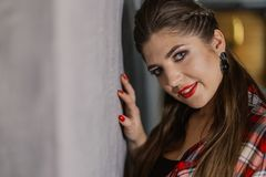 Natural light indoor portrait of young pretty girl with long dark brown hair, natural makeup and red lips. Stylish woman. Looking at you stock image