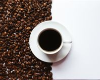 Natural light cup of espresso. This is a natural light photo of espresso surrounded on one side by roasted coffee beans royalty free stock photography