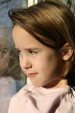 Natural light portrait of girl at window stock photography