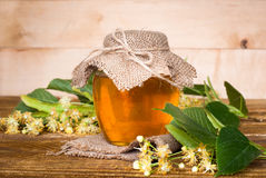 Natural linden honey. Honey in glass jar and dipper on white background with flowers Royalty Free Stock Image