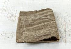 Natural linen napkin. On white wooden table stock image