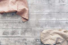 Three natural linen napkin on wooden background. Natural linen napkin on wooden background. Pastel tones royalty free stock photo
