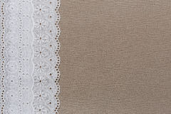 Natural linen texture with white lace. On the left side and ribbon at bottom. Empty copyspace Stock Images
