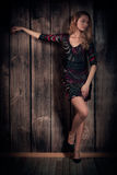 Natural looking beautiful lady in a short dress posing over wooden wall background Royalty Free Stock Image