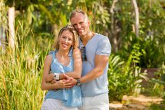 Natural looking happy couple embraced. Lovely couple in tropical resort stock image