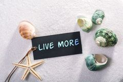 Label with live more. A natural looking label with live more written on it with sand and seashell and star Stock Photography