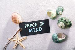 Label with peace of mind. A natural looking label with peace of mind written on it with sand and seashell and star royalty free stock photo