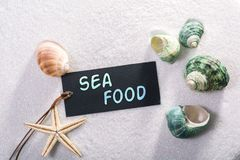 Label with sea food. A natural looking label with sea food written on it with sand and seashell and star Stock Image