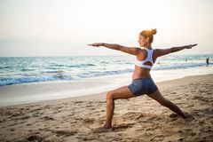 Natural looking pregnant woman practicing yoga at the seashore a Stock Photos