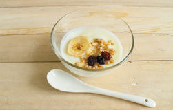 Natural low-fat yogurt with muesli and banana, raisin in the glass cup. Royalty Free Stock Photos