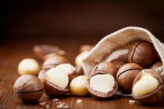 Natural macadamia nuts in canvas bag on wooden table. Natural macadamia nuts in canvas bag on wooden rustic table royalty free stock photos